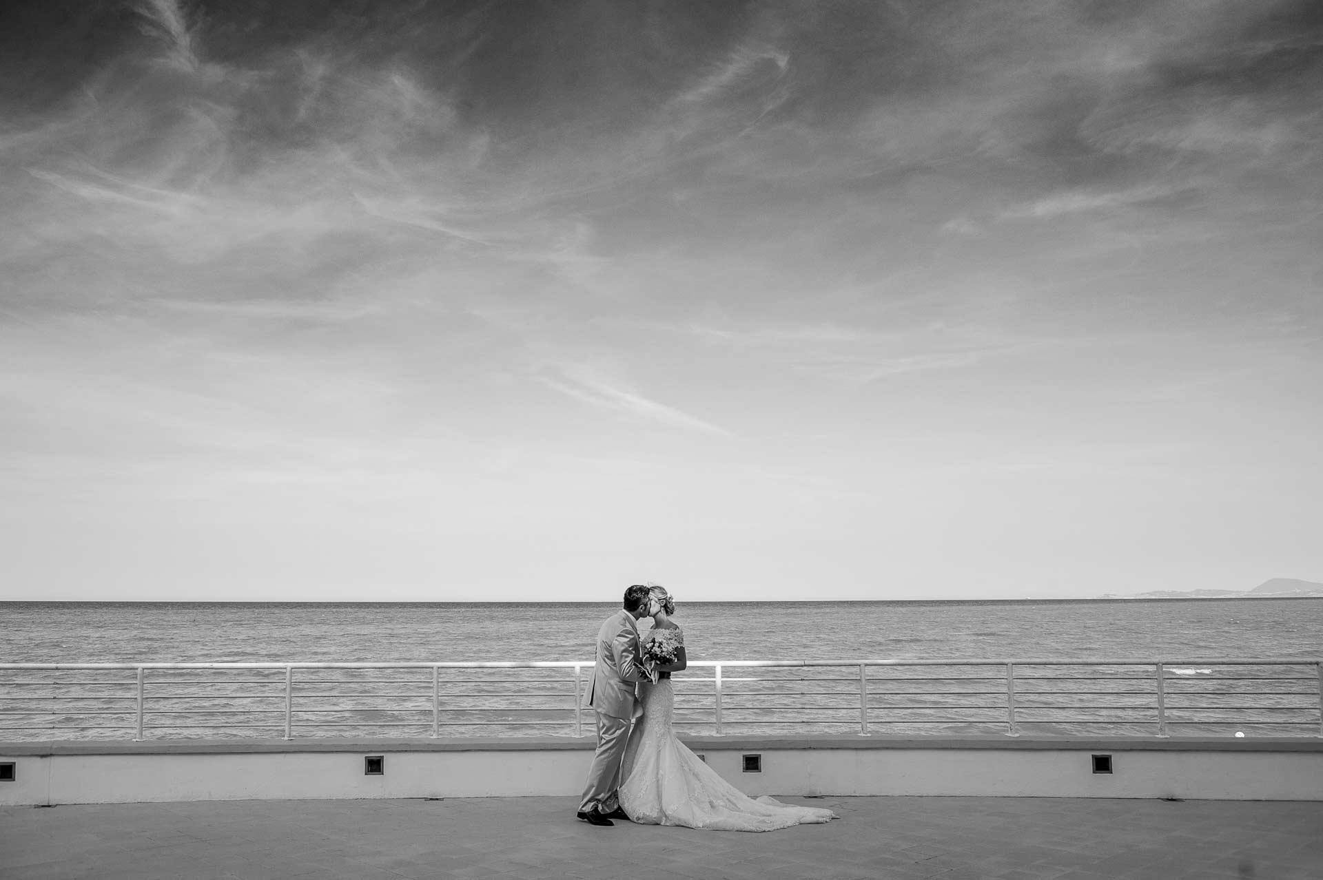 fotografo professionista italia, fotografia di matrimonio bacio sposi al mare