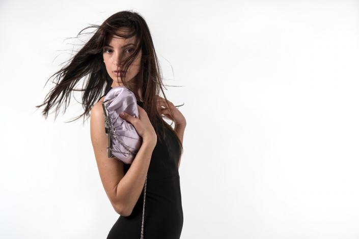 fotografia di moda e fashion, ragazza con tubino nero e borsetta