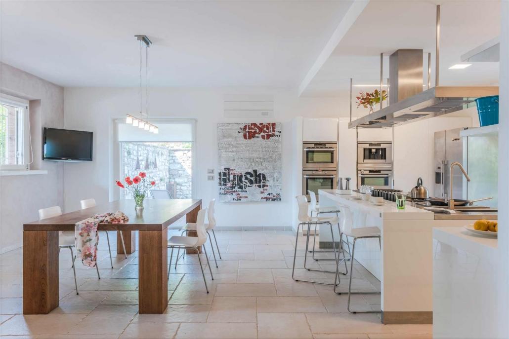 fotografia d'interni e servizio fotografico d'interni, cucina con tavolo in legno e sadute plastica bianco