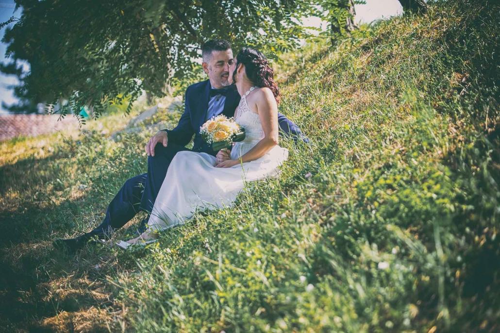 fotografo matrimonio italia, bacio sposi seduti sul prato