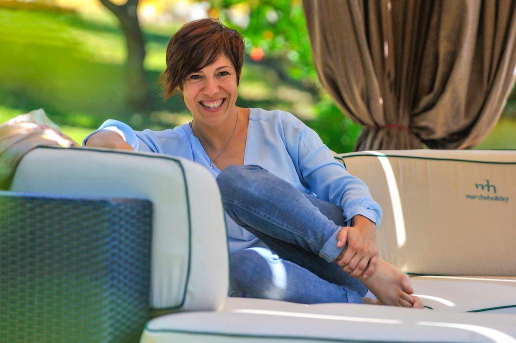 fotografia corporate e fotografia aziendale, donna sorridente sul divano nel giardino