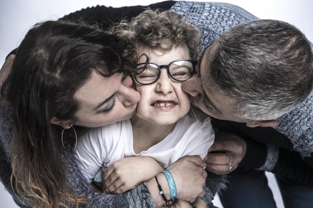 fotografo famiglia, mamma e papà che baciano il figlio